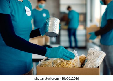 Unrecognizable female volunteer packing food in donation box while working at charity foundation.