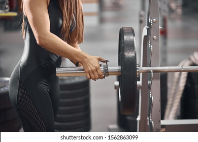 Unrecognizable fit woman keeping hand on metal barbell with one iron disc, checking, preparing place for lifting weight, sport and active people concept, close up