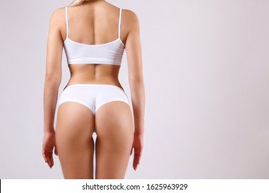 Unrecognizable fit woman in lingerie posing, showing glutes, isolated background. Back view of slim attractive female with bubble shaped buttocks in white underwear. Copy space for text, Close up