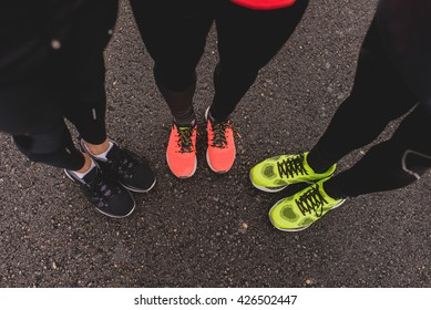 Unrecognizable friends in colorful sneakers for running