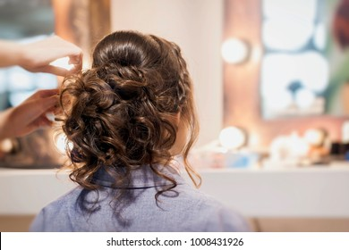 Unrecognizable girl back to us, girl in mirror at hairdresser making hairstyle, styling from long hair, hair salon, partially visible hands master. Selective focus