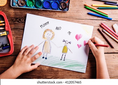 Unrecognizable girl drawing picture of her and her mother