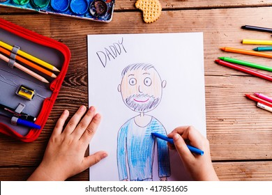 Unrecognizable girl drawing picture of her father. Wooden backgr