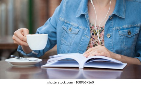Unrecognizable girl drinking coffee in an open-air summer cafe and reading a book