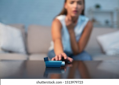 Unrecognizable Girl Reaching For Asthma Inhaler Preventing Attack Sitting On Sofa Indoor. Selective Focus, Shallow Depth