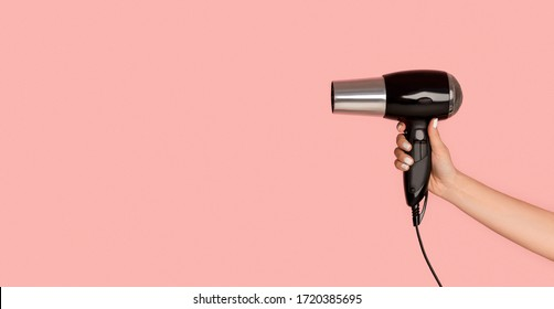 Unrecognizable girl showing hairdryer on pink background, copy space. Panorama