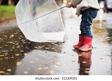 Unrecognizable girl with transparent umbrella on rainy day.