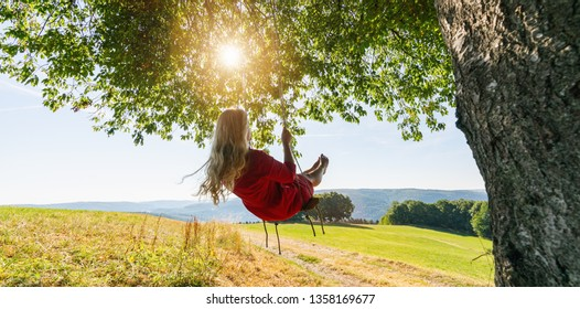 Unrecognizable girl in white dress swaying on a tree swing on peaceful evening. Lady sitting on a wooden swing and looking at golden sunset. Young woman swinging at sunrise