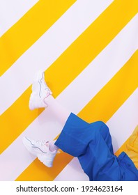 Unrecognizable girl in white sneakers on trendy yellow striped background. Spring summer minimal fashion concept