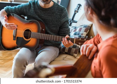 Unrecognizable guitar teacher explaining a music class to female student. Woman learning an instrument at home. Music course online concept. Indoor leisure lifestyle for young people.