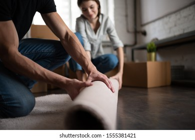 Unrecognizable guy unrolling soft carpet with help of blurred girlfriend while decorating new apartment during relocation