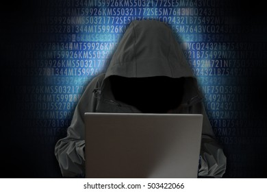 Unrecognizable hacker in front of computer â?? cybercrime concept