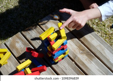 Unrecognizable kid's hand failed the jenga game by putting yellow brick in the wrong place. Colorful wooden bricks. Board game. Entertainment outdoors.