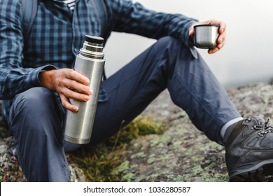 Unrecognizable  Hiker Man Holding Thermos In His Hand. Hiking Adventure Tourism Concept
