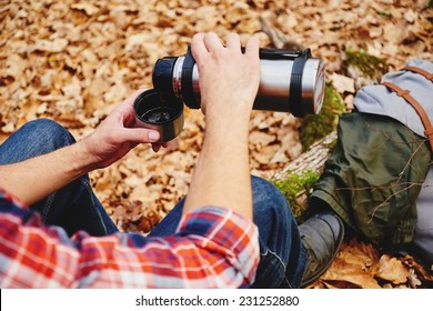Unrecognizable hiker man pours tea or coffee  from thermos in autumn forest. Hiking and leisure theme. Point of view shot