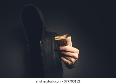 Unrecognizable hooded computer hacker offering cash money, cyber crime, blackmail and extortion concept.