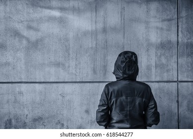 Unrecognizable hooded female person facing concrete wall as insurmountable obstacle, young adult woman in urban surrounding confronting problems and difficulties in life.