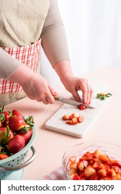 Unrecognizable housewife cutting in small pieces the strawberries. The process of making strawberry jam at home with organic fruits. Woman preparing the fruits for jam