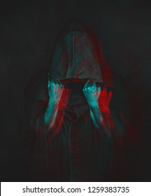 Unrecognizable human in black coat with a hood, face is not visible. Image with anaglyph effect.