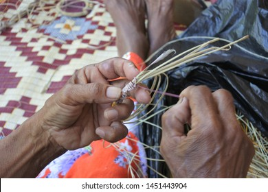 An unrecognizable Indigenous Australian Aboriginal woman basket weaving in Arnhem Land in the Northern Territory of Australia