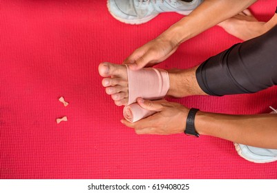 unrecognizable injured runner sitting on a red mat  Warp up before any exercise.