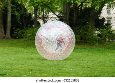 unrecognizable kid zorbing inside transparent plastic zorb ball in park