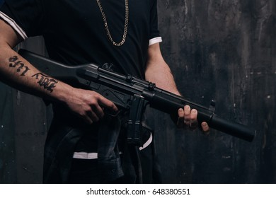 Unrecognizable killer with sniper rifle closeup studio shoot. Armed white gangster man with weapon and tattoo on dark background. Outlaw, ghetto, murderer, robbery concept