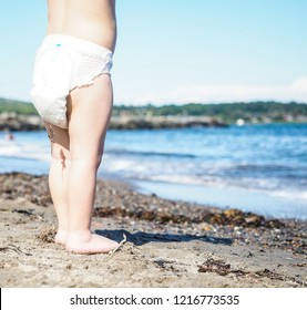 Unrecognizable little Caucasian baby boy toddler standing in sand on a beach close to waterfront