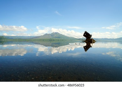Unrecognizable lone man fishing on top of isolated rock in the middle of the Lake Batur overlooking Mount Batur during cloudy blue sky in Bali Indonesia.