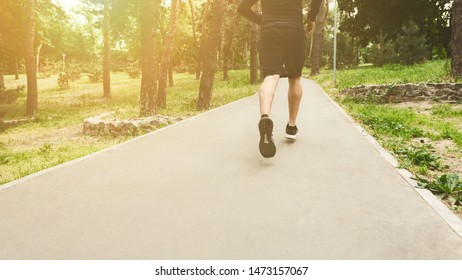 Unrecognizable male athlete jogging on treadmill in park during morning workout, panorama with copy space