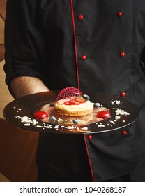 Unrecognizable male chef holding lemon cheesecake with berry spheres and caramel decoration served on dark textured plate. Exclusive dessert and haute cuisine concept