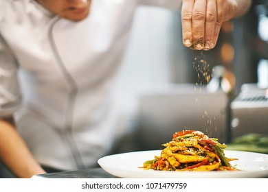 Unrecognizable male chef sprinkling spices on a dish.  Front view. Horizontal.