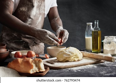 Unrecognizable male cook in apron, has dirty hands as prepares dough and mincemeat, cooks meat dumplings, breaks egg in bowl, isolated over black chalk background. Many ingridients on working table