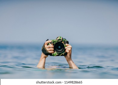 Unrecognizable male hand holding expensive professional photocamera in waterproof military case above water in ocean.  Odd photographer working in extreme dangerous conditions. Safety and protection