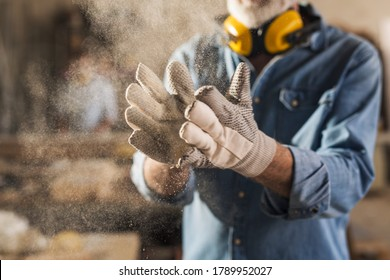 Unrecognizable male hands with work gloves on, clapping to remove sawdust