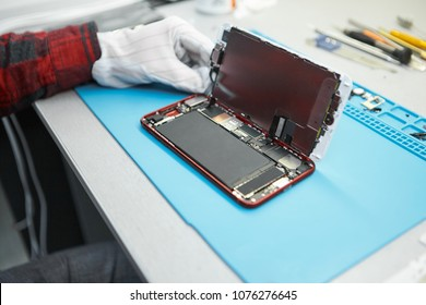 Unrecognizable male technician disassembling cell phone at his workplace, opening back cover to look inside and check small parts for faults. Repair, maintenance, computing and engineering concept