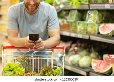 Unrecognizable man with beard holding phone in hands. Male customer leaning on trolley with vegetables and fruit. Shelves with variety of products in supermarket on background.