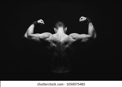 Unrecognizable man bodybuilder shows strong hands and back muscles, athletic trapezius. Black and white image, copy space, low key, studio shot, back view