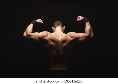 Unrecognizable man bodybuilder shows strong hands and back muscles, athletic trapezius. Low key, studio shot on black background, back view