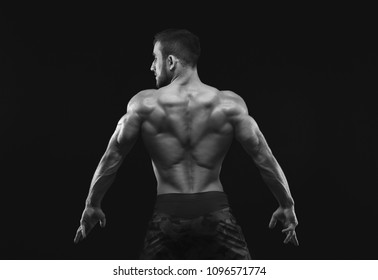 Unrecognizable man bodybuilder shows strong hands and back muscles, athletic trapezius, black and white image, studio shot on black background.