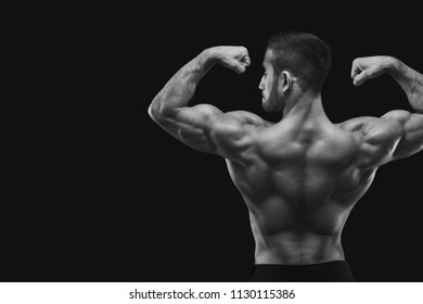 Unrecognizable man bodybuilder shows strong hands and back muscles, athletic trapezius, studio shot on black background, black and white image.