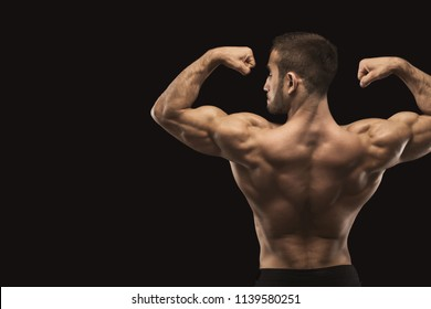 Unrecognizable man bodybuilder shows strong hands and back muscles, athletic trapezius, studio shot on black background.