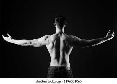 Unrecognizable man bodybuilder shows strong hands and neck muscles, athletic trapezius. Black and white, monochrome studio shot on black background.
