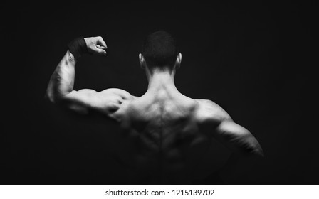 Unrecognizable man bodybuilder shows strong hands and back muscles, athletic trapezius. Low key, studio shot on black background. Black and white image, copy space