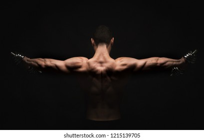 Unrecognizable man bodybuilder shows strong hands and back muscles, athletic trapezius. Low key, studio shot on black background.