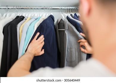 Unrecognizable man choosing jacket in his wardrobe
