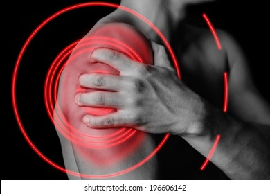 Unrecognizable man compresses his shoulder, pain in the shoulder, side view, pain area of red color