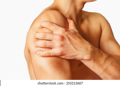 Unrecognizable man compresses his shoulder, pain in the shoulder, side view. Shoulder close-up