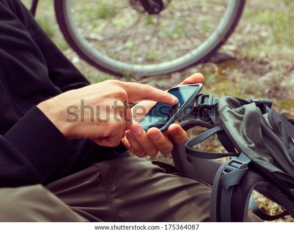 Unrecognizable man cyclist searches GPS coordinates on the mobile phone in the forest