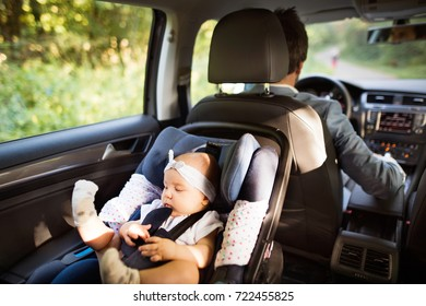 Unrecognizable man driving with a baby girl.
